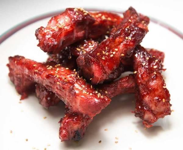 Chinese roast pork (char siu) ribs on a plate topped with sesame seeds