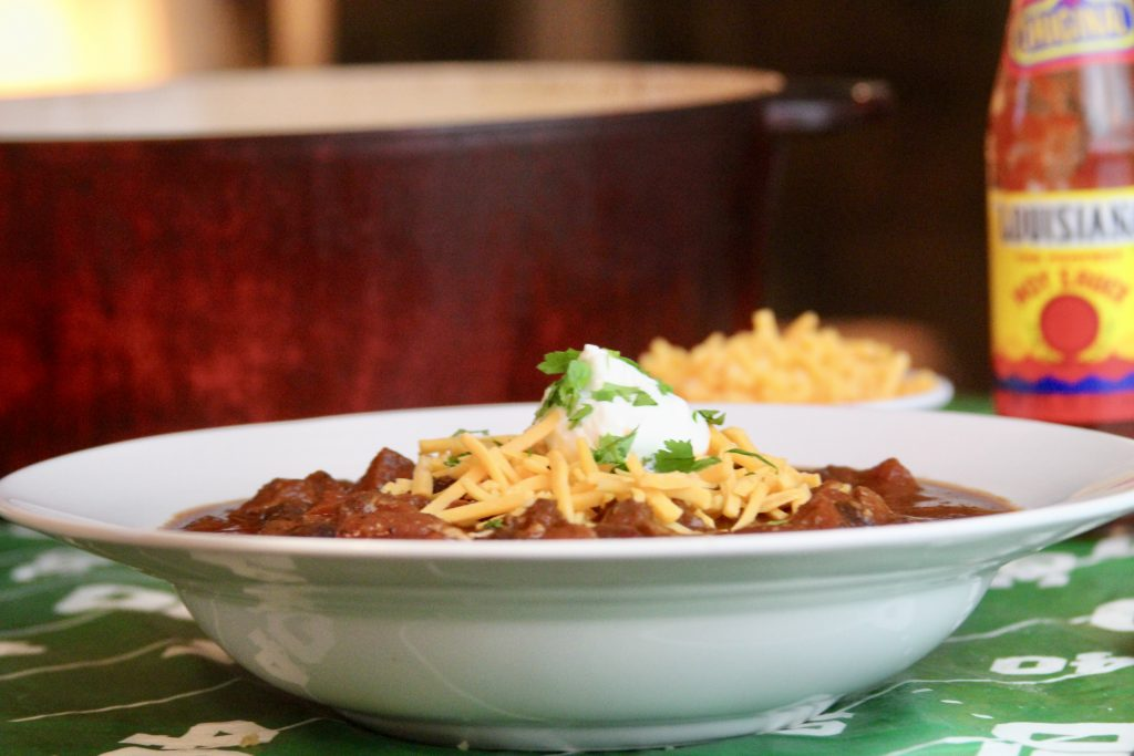 Chili con carne in a bowl with cheese and sour cream