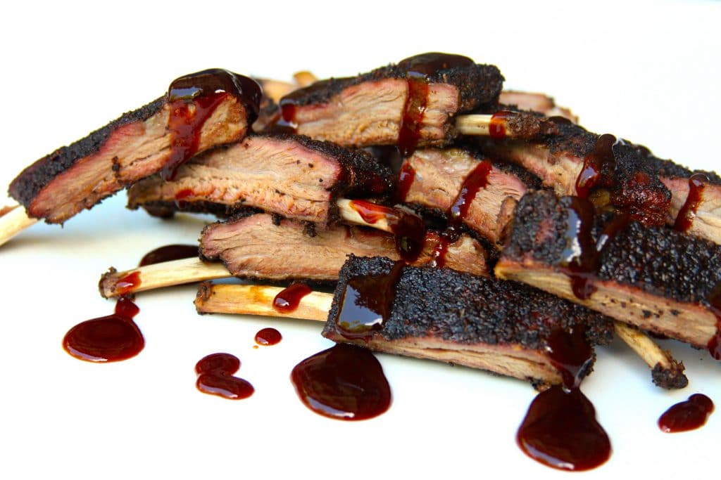 Smoked venison ribs sliced and drizzled with sauce