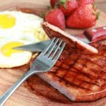 Grilled glazed ham steak plated with eggs and fruit