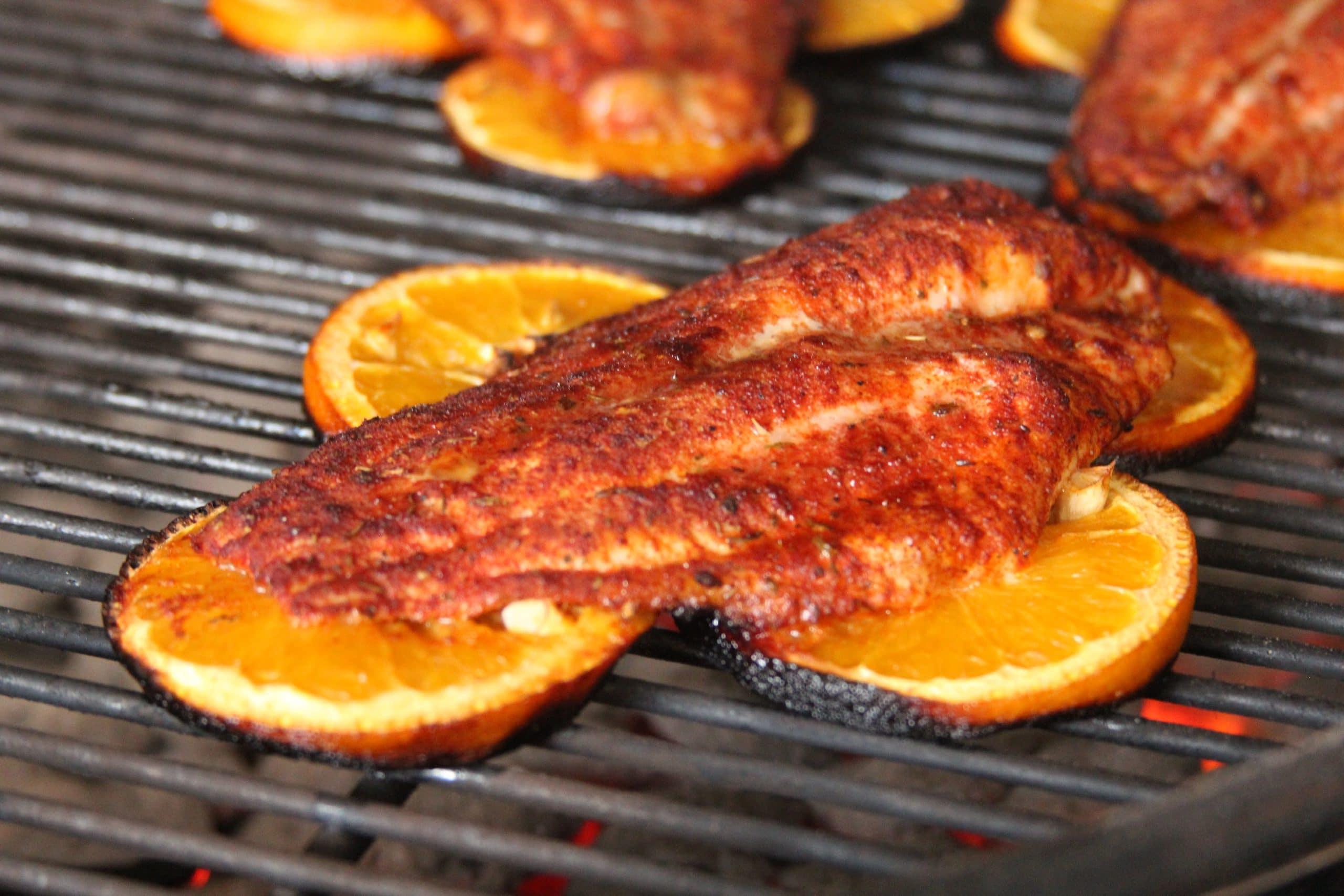 Grilling catfish fillet on orange slices