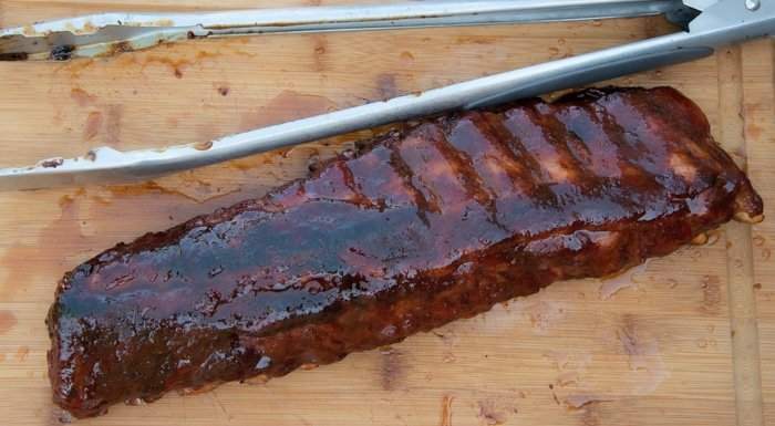 Maple glazed rack of ribs with a pair of tongs