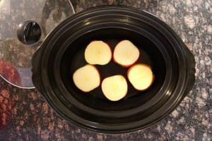 Sliced apples placed at the boom of a slow cooker
