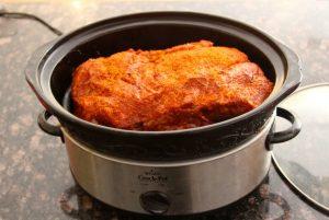 Seasoned pork butt inside of a slow cooker