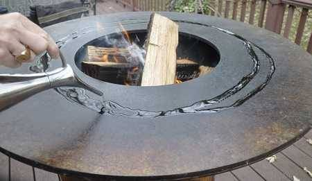 Large round firebowl filled with burning wood. A hand is pouring oil on the flat perimeter surface.