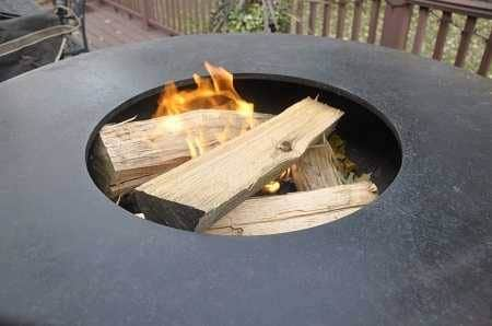 Round metal bowl filled with burning wood on an outdoor deck.