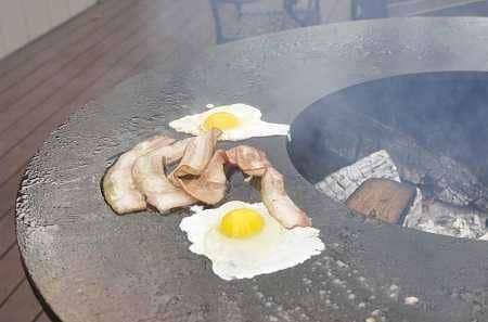 A large round fire bowl with a flat griddlw wrapped around the wood fire. Bacon and eggs are cooking on the griddle.
