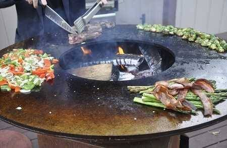A large round fire bowl with a wide griddle surface circling the hot wood fire. Meats and vegetables are cooking all around the griddle. A man is cutting into a steak with a large knife.