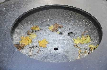 Large round metal bowl with autumn leaves inside.