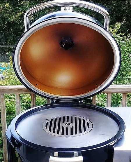 Kamado with dome open to show heavy metal round griddle inside. On an outdoor deck with green bushes in the background.