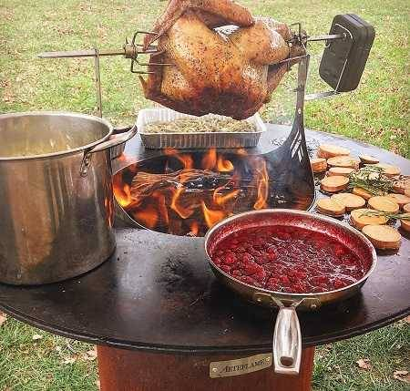 A large round fire bowl with a flat griddle surface wrapped around the central wood fire. Pots and pans filled with food are cooking on the griddle and a chicken on motorized rotisserie is hovering over the fire.