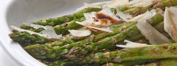 Grilled asparagus spears topped with cheese shavings