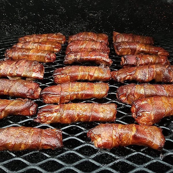 Individual ribs, wrapped in bacon, shine on the grill