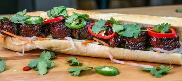 Baguette, split and filled with meat, red and green jalapenos, and garnished with cilantro