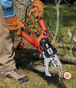 Man with heavy leather gloves using a smallish chain saw to cut tree branches laying on grass.