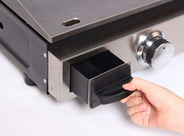 A hand pulls out a small drawer from a shiny metal box