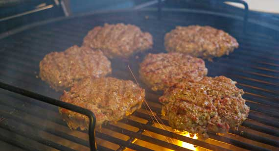 Hamburgers sizzling on a grill.