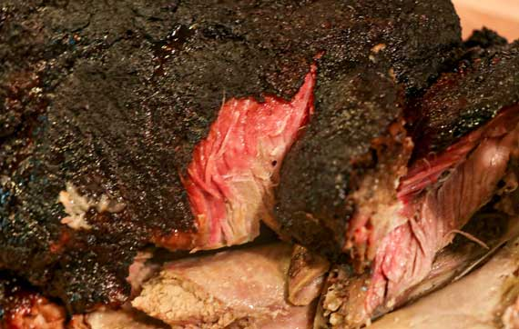 Dark, smoked meat with a pink smoke ring.