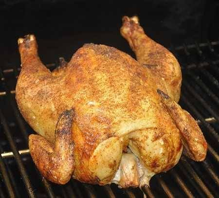 Golden brown whole chicken on a cooking grate.