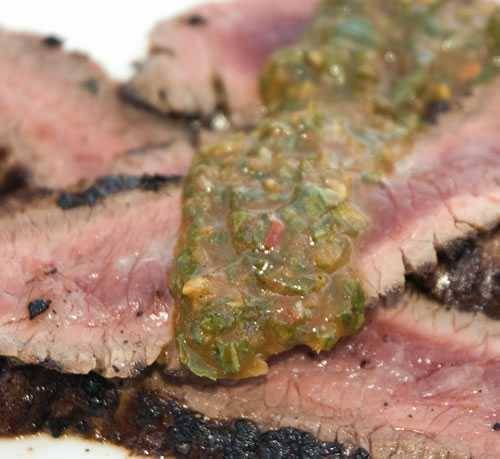Grilled and sliced steak topped with chimichurri sauce
