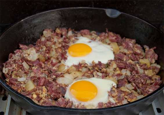 Skillet with corned beef hash topped with eggs