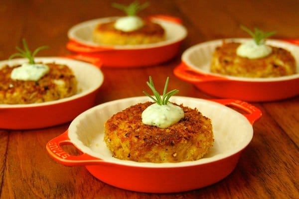 Grilled crab cakes in serving dishes topped with aioli