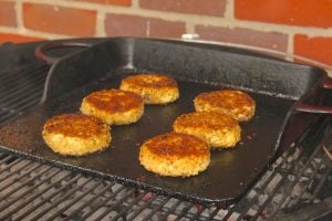 Crab cakes cooking on a griddle
