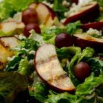Grilled apple slices and red grapes on a bed of lettuce