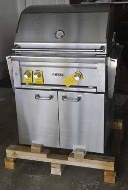 Shiny stainless steel gas grill with three gas knobs in front with yellow tags hanging from them. The grill is on a wood shipping pallet.
