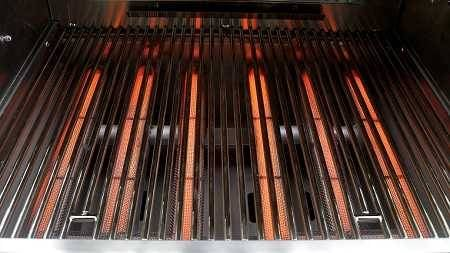 Six glowing red gas burners in a gas grill covered by steel rod grill grates.