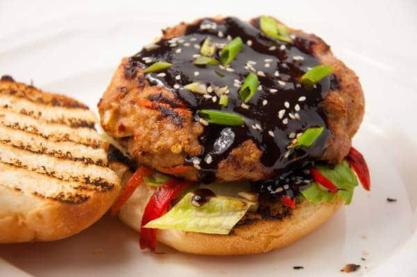Burger covered in sauce, sitting on a bun with lettuce and tomato