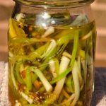 slender green ramps with liquid and whole spices in mason jar