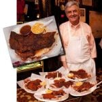 An aproned chef stands next to plates of Memphis style dry ribs