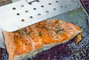 Salmon being flipped with a spatula