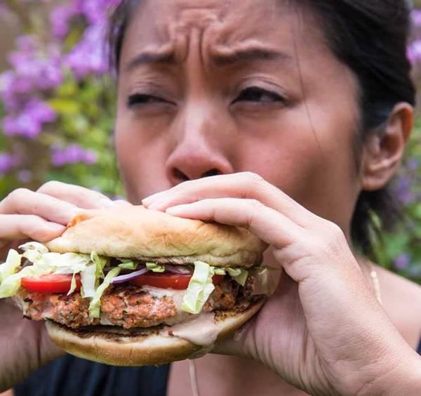 Woman eating a salmon sausage sandwich