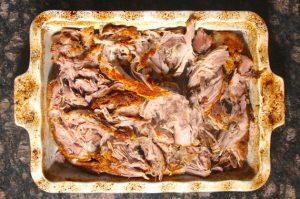 Shredded slow cooker pork butt in serving dish