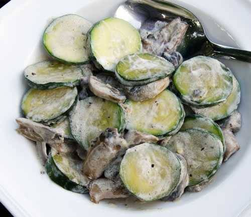 Slices of zucchini and chunks of mushrooms coated in sour cream