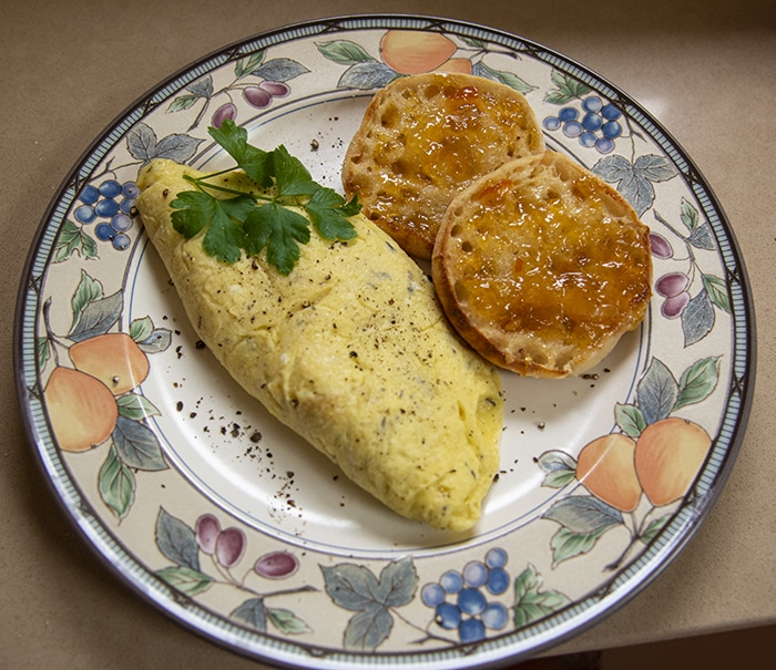 An omelet with fresh herbs plated with a buttered English muffin